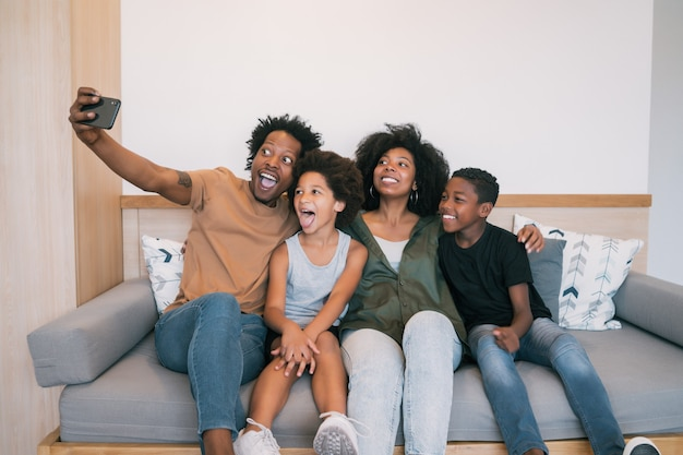 自宅で携帯電話と一緒に自分撮りをしているアフリカ系アメリカ人の家族の肖像画。家族とライフスタイルの概念。