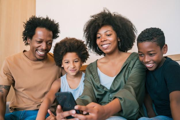 집에서 휴대 전화와 함께 selfie를 복용하는 아프리카 계 미국인 가족의 초상화. 가족 및 라이프 스타일 개념.
