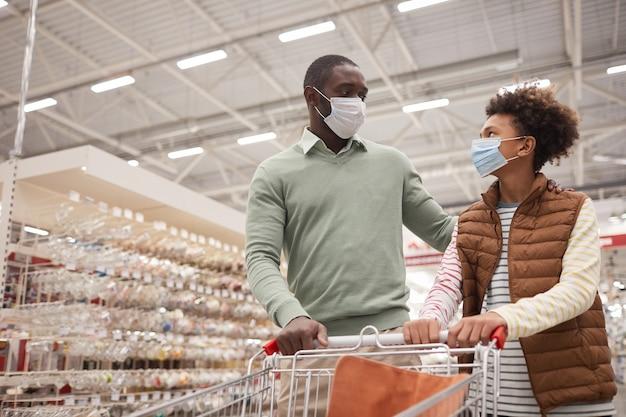Портрет афро-американских отца и сына в масках в супермаркете, таща тележку для покупок, копировальное пространство