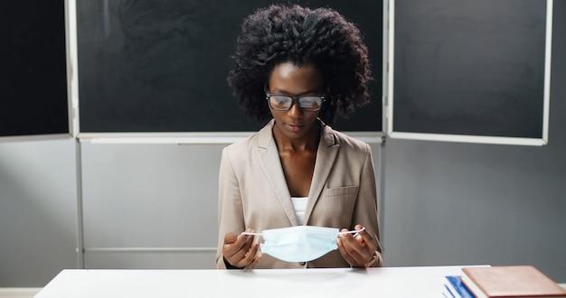 Портрет афро-американской учительницы в очках, берущей медицинскую маску, сидя за столом в классе в школе и улыбаясь в камеру. женщина-преподаватель носить защиту. концепция коронавируса.