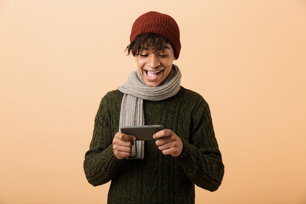 노란색 벽 위에 절연 스마트 폰에서 비디오 게임을 모자와 스카프를 착용하는 아프리카 계 미국인 게이머 소년의 초상화