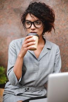 ベンチに座って、夢のようにコーヒーを飲みながら眼鏡をかけてアフリカ系アメリカ人の女の子の肖像画