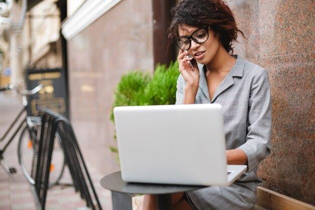 ベンチに座って、ラップトップで作業しながら彼女の携帯電話で話しているメガネのアフリカ系アメリカ人の女の子の肖像画