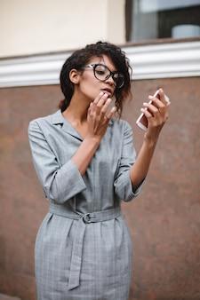 手に携帯電話で立っている眼鏡のアフリカ系アメリカ人の女の子の肖像画