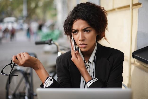 眼鏡と携帯電話を手にカフェのテーブルに座っているアフリカ系アメリカ人の女の子の肖像画