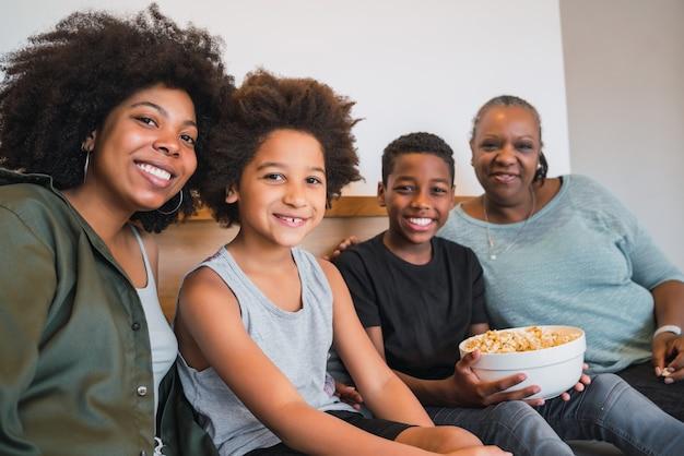 カメラを見て、自宅のソファに座って笑っているアフリカ系アメリカ人の祖母、母と子の肖像画。家族とライフスタイルの概念。