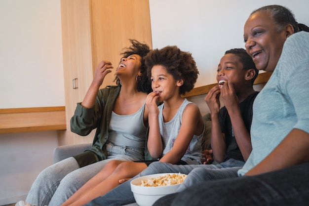 映画を見たり、自宅のソファに座ってポップコーンを食べているアフリカ系アメリカ人の祖母、母と子の肖像画。家族とライフスタイルの概念。