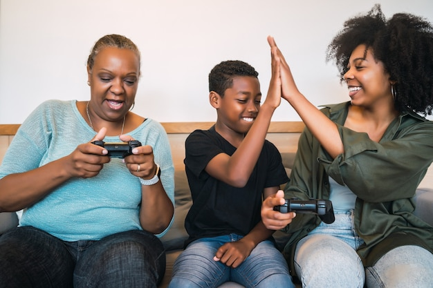 アフリカ系アメリカ人の祖母、母と息子が自宅で一緒にビデオゲームをプレイする肖像画。技術とライフスタイルのコンセプト。