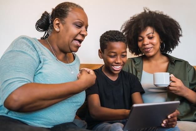 アフリカ系アメリカ人の祖母、母と息子が自宅でデジタルタブレットでselfieを取っている肖像画。技術とライフスタイルのコンセプト。