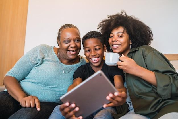 Портрет афро-американской бабушки, матери и сына, делающих селфи с цифровым планшетом дома.