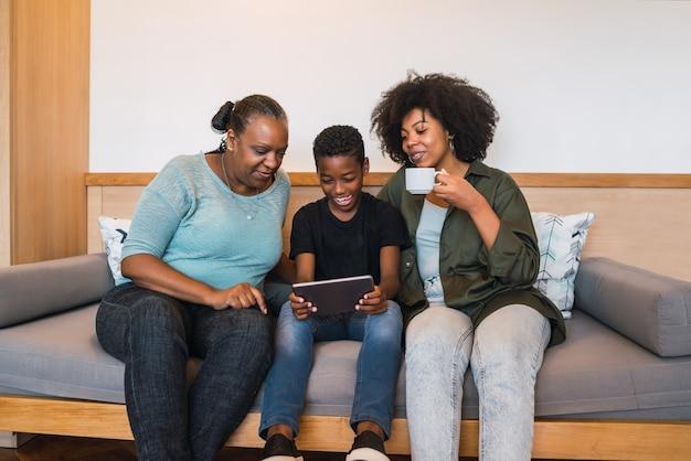 집에서 디지털 태블릿을 사용하는 아프리카 계 미국인 할머니, 어머니와 아들의 초상화
