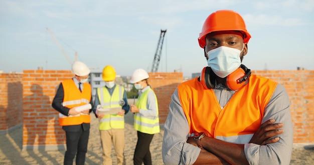 建設時に屋外に立ってカメラを見ているカスクと医療マスクのアフリカ系アメリカ人のハンサムな若い男のコンストラクターの肖像画。ヘルメットの建物の上部にある男性ビルダー。コロナウイルス。