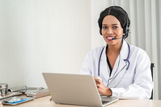 Портрет афро-американских счастливый улыбающийся молодой врач в гарнитуру, консультирование пациента по телефону. медицинский колл-центр онлайн концепция