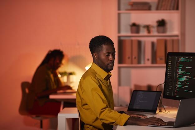 Портрет афро-американского ит-разработчика, пишущего код на экранах нескольких компьютеров во время работы в офисе, копирование места