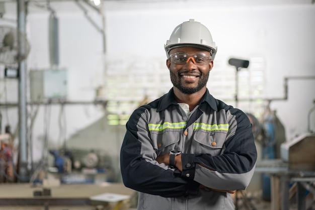 工業工場で均一な笑顔と立っているクロスアームのアフリカ系アメリカ人男性エンジニアの肖像画