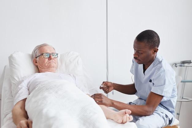 Портрет афро-американской медсестры, ухаживающей за пожилым мужчиной, лежащим на больничной койке с белым, копией пространства