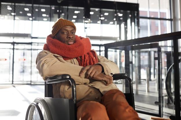 Портрет афроамериканца в инвалидной коляске, смотрящего в камеру в доступном торговом центре или городской городской станции, копией пространства