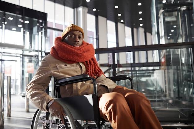Портрет афроамериканца в инвалидной коляске, смотрящего в камеру при входе в доступный торговый центр или станцию метро