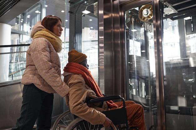 Портрет афро-американского мужчины в инвалидной коляске, использующего доступный лифт, с молодой женщиной, помогающей в городских условиях города, копией пространства