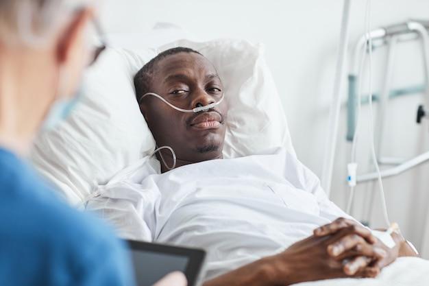 Портрет афро-американского мужчины, лежащего на больничной койке и смотрящего на врача, копией пространства