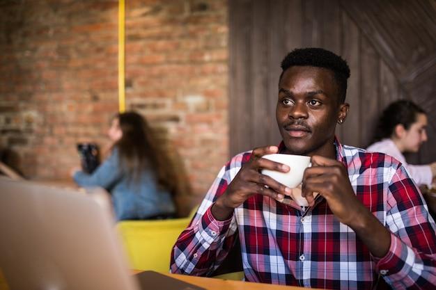 カフェに座っているとラップトップに取り組んでいるアフリカ系アメリカ人の肖像画。