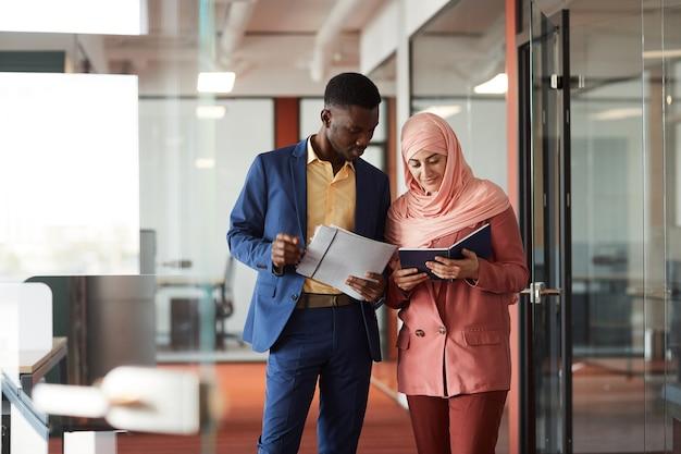若いイスラム教徒の実業家と話し、オフィスのインテリア、コピースペースでカメラに向かって歩いている間ドキュメントを保持しているアフリカ系アメリカ人の男性の肖像画