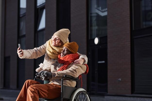 車椅子を使用して、都市の屋外で支援している若い女性と一緒に自分撮り写真を撮るアフリカ系アメリカ人の男性の肖像画、コピースペース