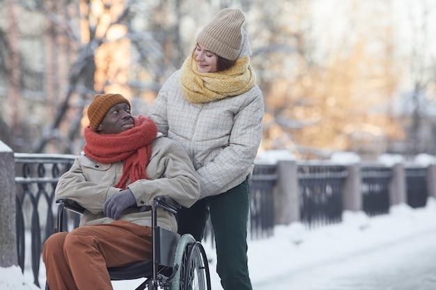 Портрет афро-американского мужчины, использующего инвалидную коляску, развлекающегося на открытом воздухе зимой с улыбающейся молодой женщиной, смотрящей на него и помогающей, копией пространства