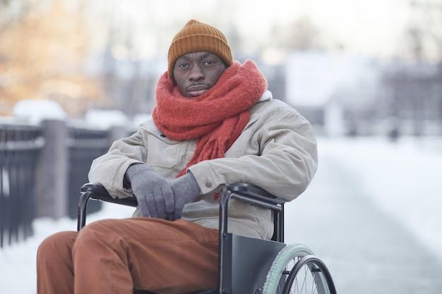 Портрет афро-американского мужчины, использующего инвалидную коляску на открытом воздухе зимой и смотрящего в камеру, копией пространства