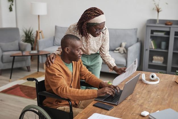 Портрет афро-американского мужчины, использующего инвалидную коляску, работающего из дома, с женой, оглядывающейся через плечо, копией пространства