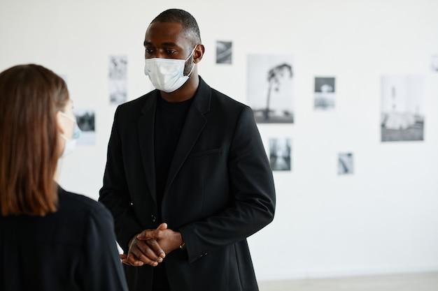 現代のギャラリー、コピースペースで女性とアートを議論しながらマスクを身に着けているアフリカ系アメリカ人の男性の肖像画