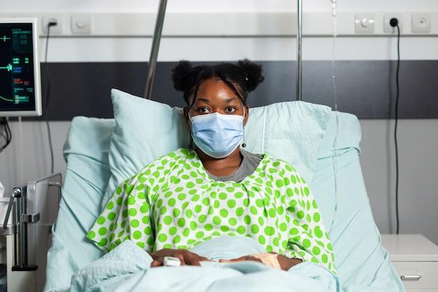 病棟のベッドに座っているカメラを見ているフェイスマスクを持つアフリカ系アメリカ人患者の肖像画。病気、医療機器との相談を待っている病気の若い女性