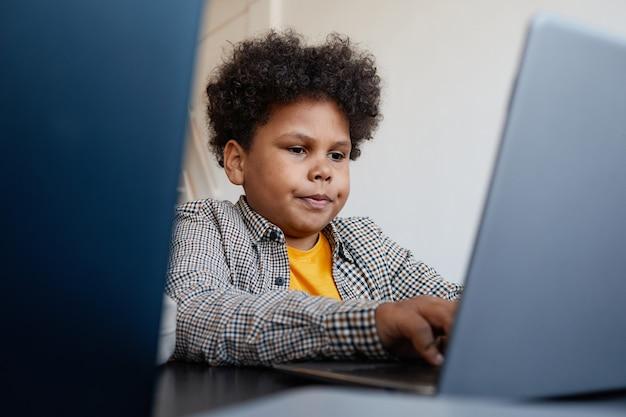学校のitクラス、コピースペースでラップトップコンピューターを使用してアフリカ系アメリカ人の男子生徒の肖像画