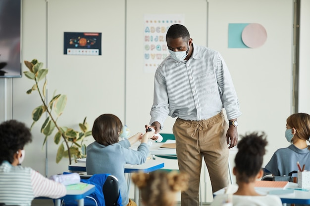 학교 교실에서 아이들의 손을 소독하는 아프리카계 미국인 교사의 초상화, 코비드 안전 조치, 복사 공간