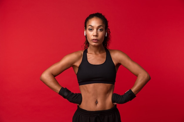 彼女の手にスポーツ包帯を持って立っている黒いスポーツウェアのアフリカ系アメリカ人女性20代の肖像画、赤い壁に隔離