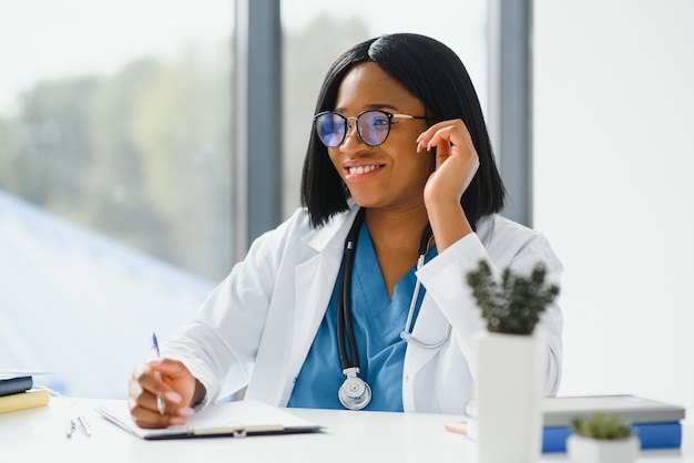 Портрет афро-американской женщины-врача, улыбаясь в больнице