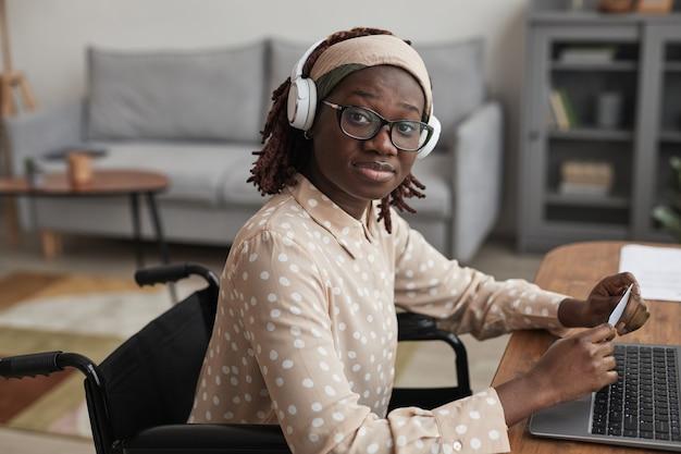 ラップトップを介して車椅子のオンラインショッピングでカメラを見て、スペースをコピーするアフリカ系アメリカ人の女性の肖像画