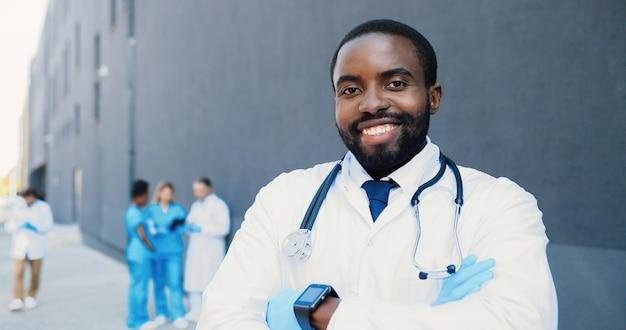 Портрет афро-американского молодого врача со стетоскопом, глядя на камеру и скрещивая руки. красивый мужчина-врач улыбается. многонациональные медики на фоне. медик в белом халате. долли стреляла.