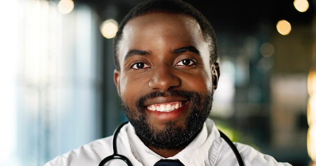 カメラを見て元気に笑って聴診器を持つアフリカ系アメリカ人の若い男の医者の肖像画。ハンサムな幸せな男性医師の笑顔。クリニックの白いガウンのメディック。屋内。