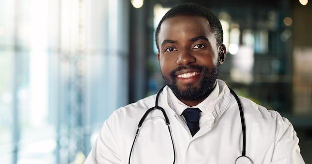 カメラを見て元気に笑って聴診器を持つアフリカ系アメリカ人の若い男の医者の肖像画。ハンサムな男性医師の笑顔。白いガウンのメディック。屋内。