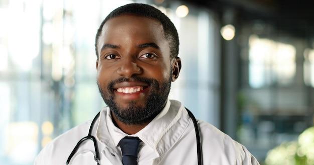 元気にカメラに微笑んで聴診器を持つアフリカ系アメリカ人の若い男の医者の肖像画。ハンサムな幸せな男性医師の笑顔。クリニックの白いガウンのメディック。屋内。