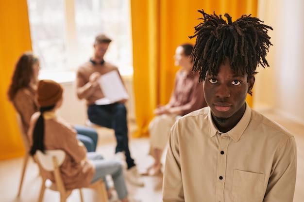 지원 그룹에서 치료 세션 동안 카메라를 보고 있는 아프리카계 미국인 젊은 남자의 초상화, 복사 공간