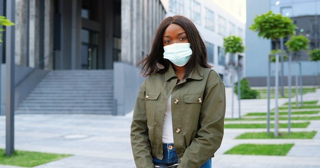 カメラを見て、都会の通りに立っている医療マスクのアフリカ系アメリカ人の若いスタイリッシュなきれいな女性の肖像画。パンデミック時の街の屋外の美しい女性。コロナウイルス封鎖。