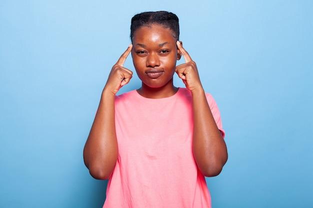 의심이 있는 사원에 손가락을 대고 있는 아프리카계 미국인 젊은 여성의 초상화