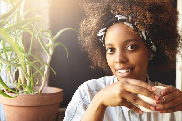 カフェテリアで素敵な時間を過ごして幸せな顔でホットコーヒーや紅茶のカップを保持している白いスタイリッシュなデニムシャツに身を包んだアフロのヘアカットを持つアフリカ系アメリカ人の若い女性の肖像画