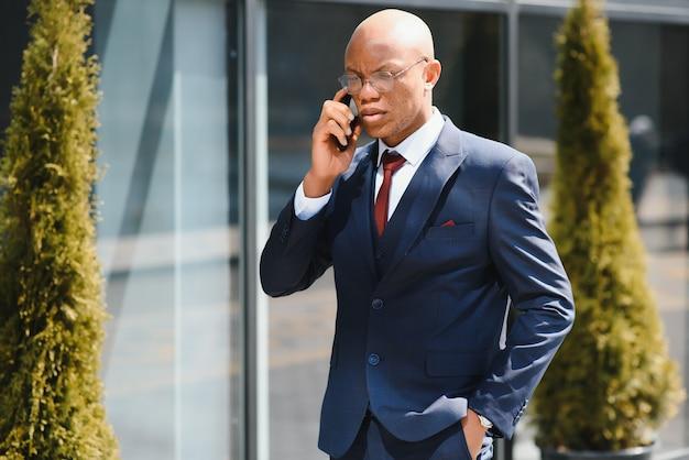 Портрет руководителя африканского бизнеса гуляет и разговаривает по мобильному телефону