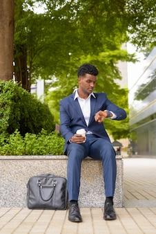 腕時計から時間をチェックし、都市の垂直全身ショットで屋外でコーヒーカップを持ち帰るアフリカの実業家の肖像画