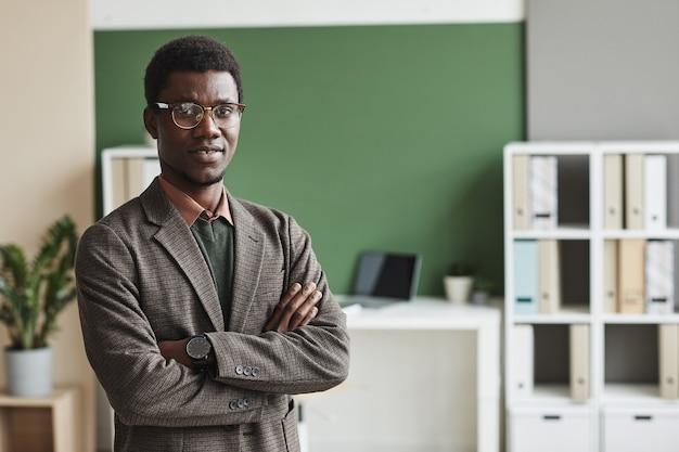 Портрет африканского бизнесмена в стильном костюме, стоящего со скрещенными руками и улыбающегося в офисе