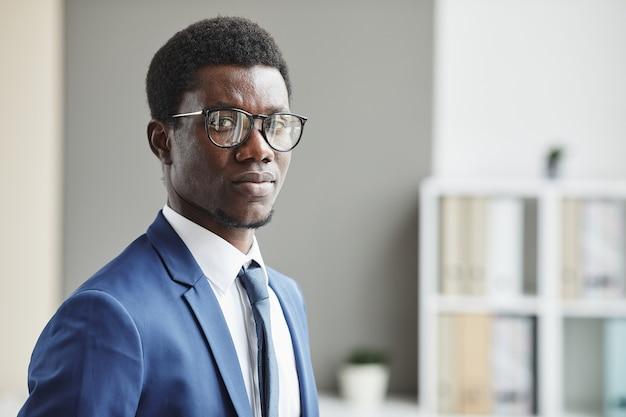Портрет африканского бизнесмена в костюме, стоящего в офисе