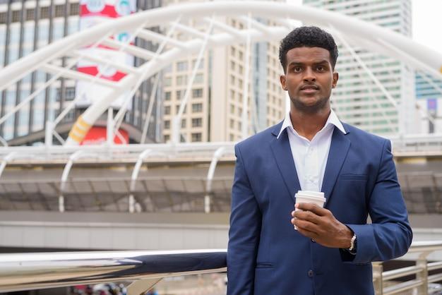 持ち帰りコーヒーカップ、水平ショットを保持している屋外でアフリカの実業家の肖像画